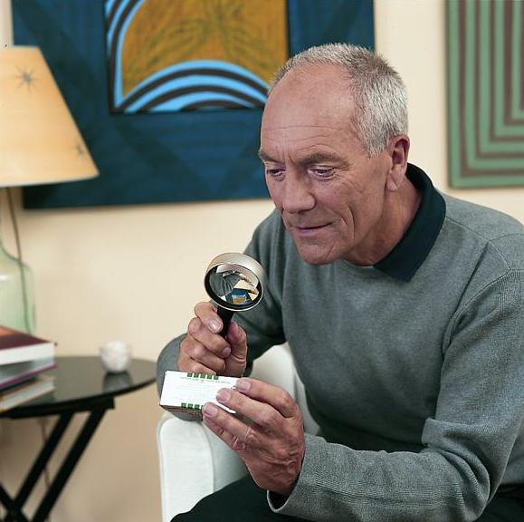 Bild eines Mannes, der mit Lupe eine Medikamentenpackung liest