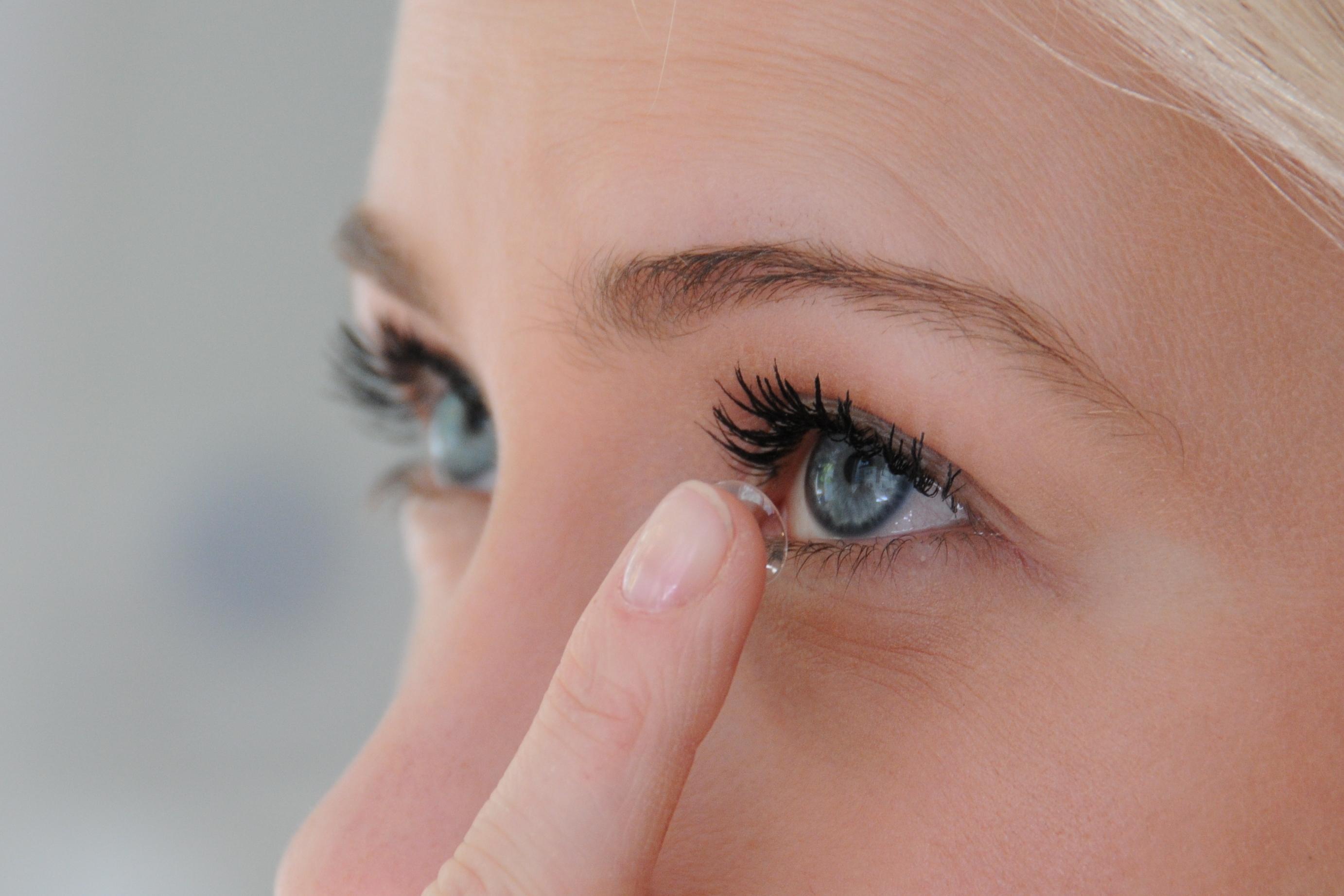 Foto einer Frau, die sich eine Kontaktlinse einsetzt